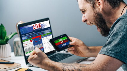 Guy being happy winning a bet in online sport gambling application on his mobile phone