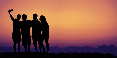 Group taking selfie on sunset with copy space