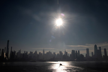 A ferry boat passes the midtown Manhattan skyline on the Hudson River in the early morning in New York City