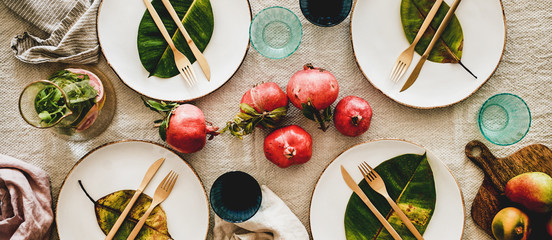 Fall, Autumn table styling for holiday dinner. Flat-lay of dinnerware with fruit and leaves for...