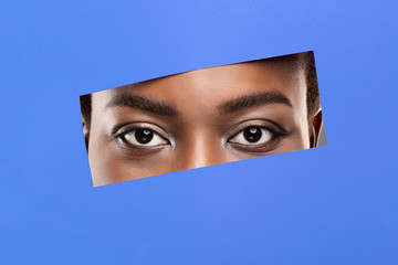 Fototapete - Afro woman's eyes without makeup peeking from hole in blue paper