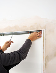 Carpenter adjusting by hand with a wrench the upper guide of a new white sliding door