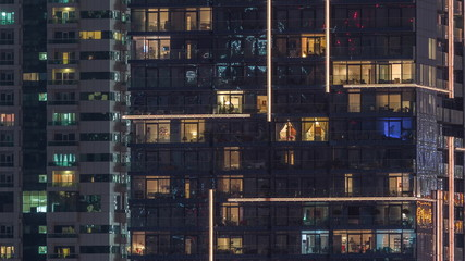 Rows of glowing windows with people in apartment building at night.