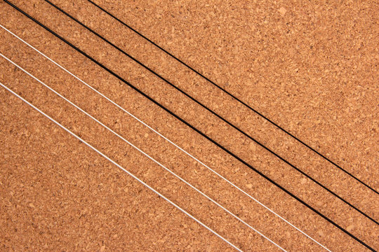 Classical guitar strings on balsa wood texture background
