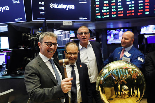 CEO of Kaleyra, Dario Calogero, laughs while holding a celebratory gavel during the company's IPO above the floor of NYSE shortly after the opening bell in New York