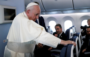 Pope Francis listens to questions during a news conference onboard the papal plane on his flight back from a trip to Thailand and Japan