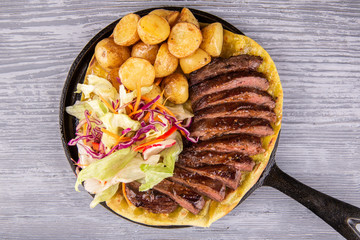 Roasted meat on a pan, with potatoes roasted, fresh salad on a lavash