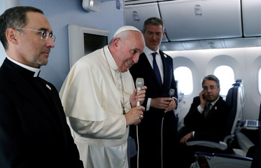 Pope Francis speaks during a news conference onboard the papal plane on his flight back from a trip to Thailand and Japan