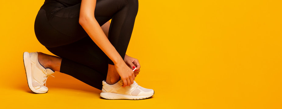 Unrecognizable Lady Lacing Shoes Before Fitness Workout, Yellow Background, Panorama