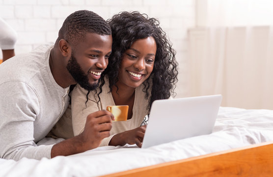 Happy african american couple shopping online, using laptop and credit card in bed, empty space