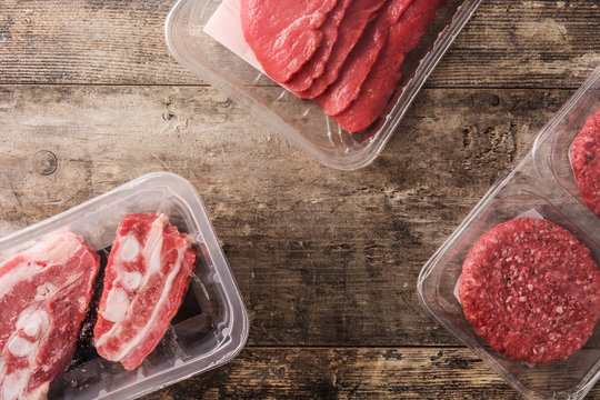 Different types of meat packaged in plastic on wooden table. Top view