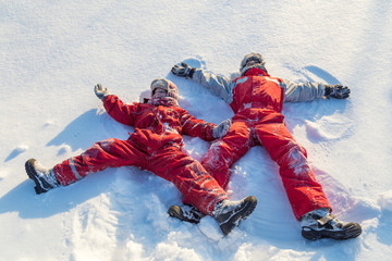 Two boys in winter clothes making snow angel