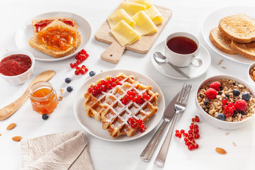breakfast with granola berry nuts, waffle, toast, jam, chocolate spread and tea