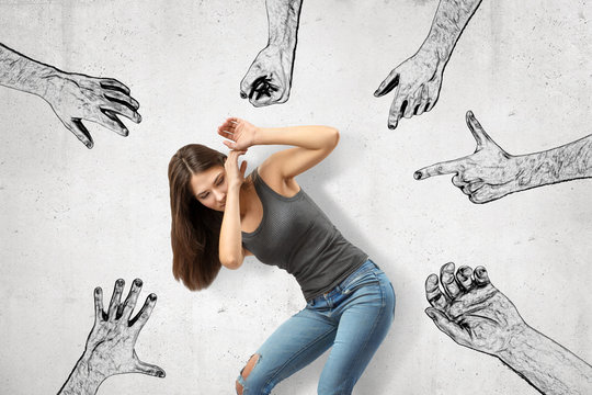 Young girl bending down covering her face with her hands trying to protect herself from mens' fists, finger guns and hands pointing at her.