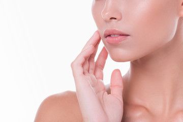 Close-up of half portrait of a beautiful young girl with clear and radiant skin on her face and neck posing on a white background. Concept of proper skin care and salon treatments. Advertising space