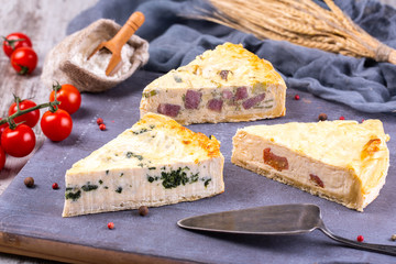 Pies in range on wooden board with cherry tomatoes