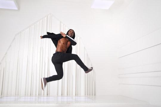 Elegant black man dancer in black clothes jumping in a bright room.