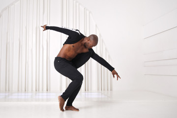 Elegant black man dancer in black clothes is dancing in a bright room.