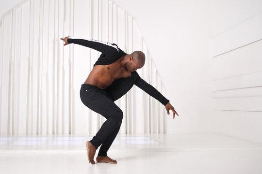 Elegant black man dancer in black clothes is dancing in a bright room.