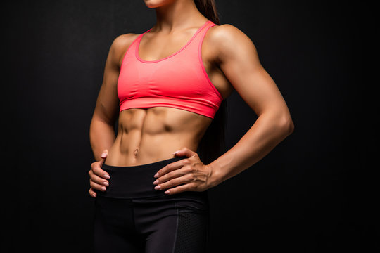 Cropped shot of a beautiful female with fit and toned strong body on black background.