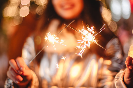 Young woman holding sparklers while standing against Christmas lights in city