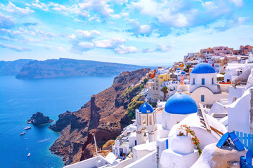Beautiful Oia town on Santorini island, Greece. Traditional white architecture  and greek orthodox churches with blue domes over the Caldera, Aegean sea. Scenic travel background. Fotomurales