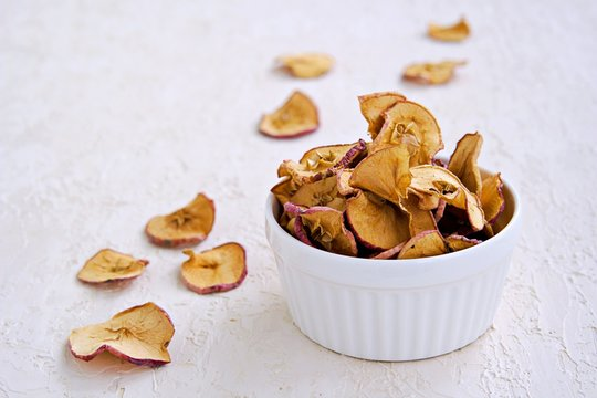 Organic apple chips or dried apples in a white ceramic form on a light concrete background. Healthy snacks. Harvest apples. Thanksgiving Day.
