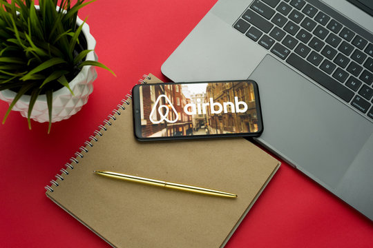 Tula, Russia, november 26, 2019: Airbnb logo on the smartphone screen is placed on the Apple macbook keyboard on red desk background.