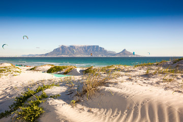 Beach dunes and kite surfers at Blouberg beach with in the background Cape Town and Table Mountain
