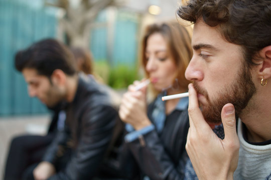 Young people smoking outdoors sitting on a bench. Youth addiction problem smoking cigarettes concept. Focus on man face, blurred friends
