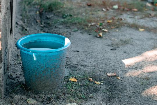 Blue plastic bucket full of water in the garden. Dirty garden tools