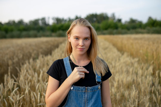 Smiling young woman holding wheat in field