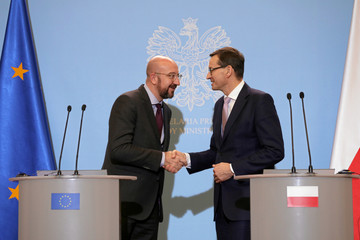 President-elect of European Council Charles Michel and Poland's Prime Minister Mateusz Morawiecki shake hands during a news conference in Warsaw
