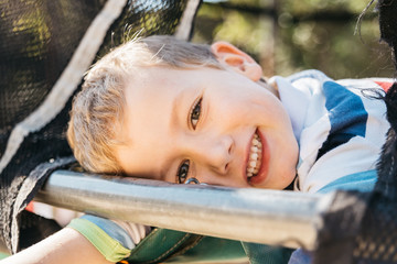 Young blond 5 year old smiling at camera enjoying his childhood while playing happy and enjoying spring.