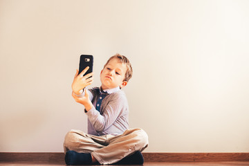 Young twink boy taking a selfie sitting at home, concept of new technologies.