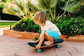 5 year old boy practicing skate in his back yard afraid of falling.