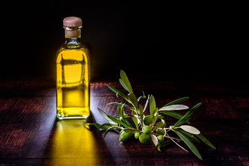 Bottle with virgin olive oil next to a bouquet of raw olives on dark background.