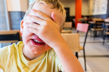 Child covering his surprise face with his hand while smiling.