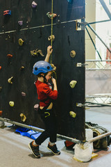 Child on the walls of a climbing wall with the help of a safety rope