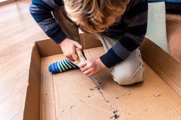 Child playing with a cardboard box and a saw to build.