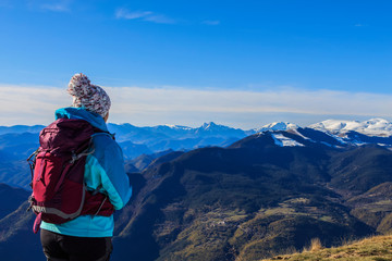 Girl with hat and backpack looking at the snowy mountains.Concept people