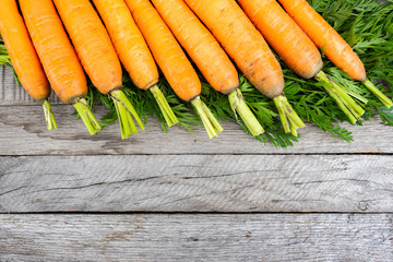 fresh carrots on wooden table after harvesting, cooking for vegetarians, healthy food. Growing vegetables in garden