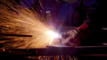 Worker in gloves cutting sheet metal in fabrication factory. Gas metal cutting with acetylene or oxygen torch. Bright sparks and smoke from exothermic reaction between oxygen and the workpiece in indu