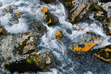 Strong mountain river. Rapid flow of stream among rocks. Blue stream of water seethes in rocks