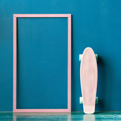 Blank plastic pink skateboard with blank pink frame on the floor against blue wall