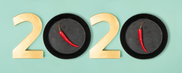 2020 eve top view new year number and pans with hot chillie pepperes as zero numbers. Flat lay style on neon mint background.