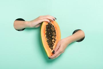 Female hands hold fresh papaya through a hole on neon mint background.