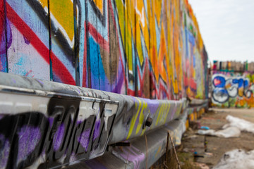 Lots of colorful graffiti on a wooden wall and a crash barrier