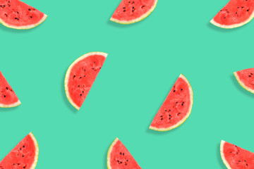 Flat lay of watermelon half slices on mint background. Watermelon pattern.