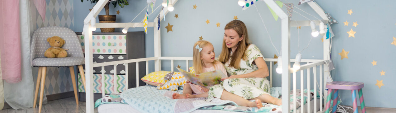 Cute 3 years old girl and her young mother are reading a book and smiling while sitting in decorated house bed at bedroom before bedtime